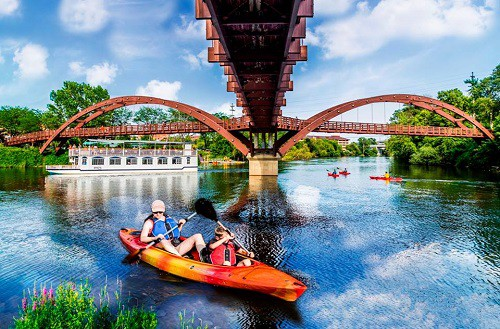 The Tridge, kayakers, and a riverboat on the Tittabawassee River, coutsey of the City of Midland